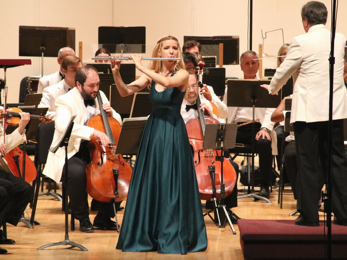 female with blond hair in green ball gown playing flute with orchestra