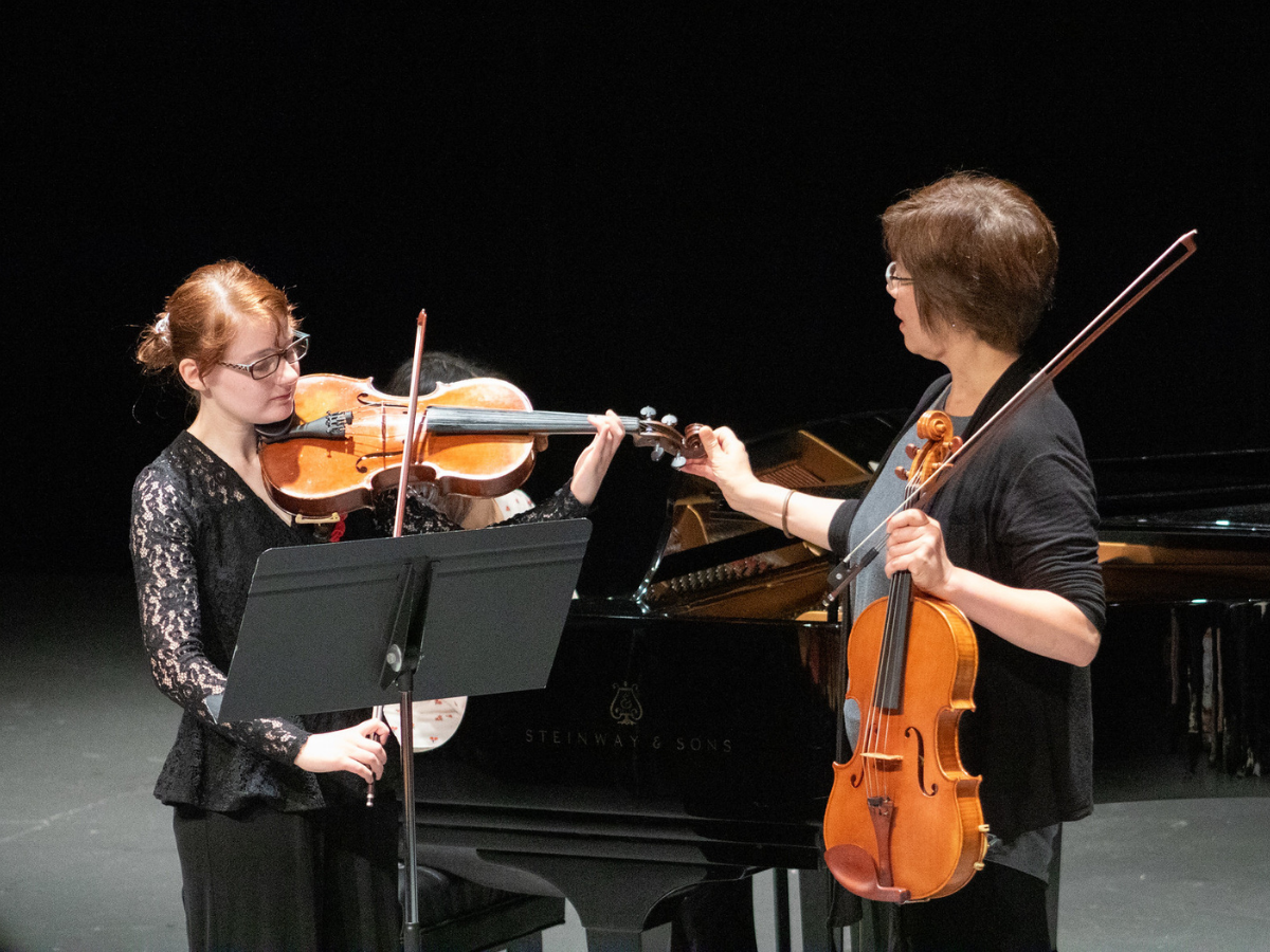 famle with red hair and glassess playiong viola with teach holding viola
