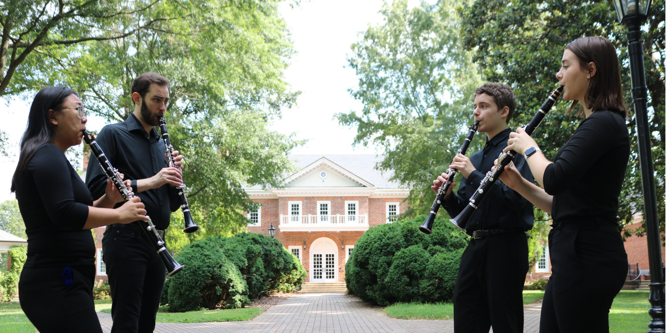 four musicians playing clarinets outside