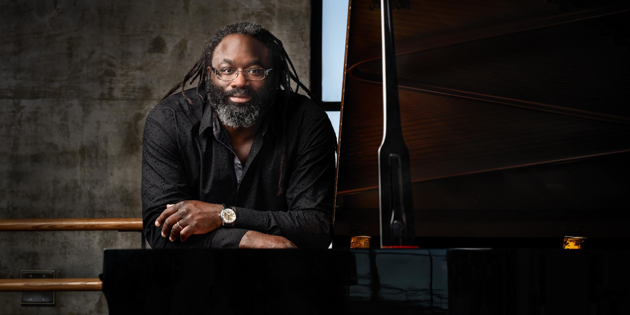 black man with dreadlocks at a grand piano