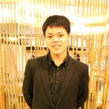 Asian Male in black suite on front of a gold wallpaper