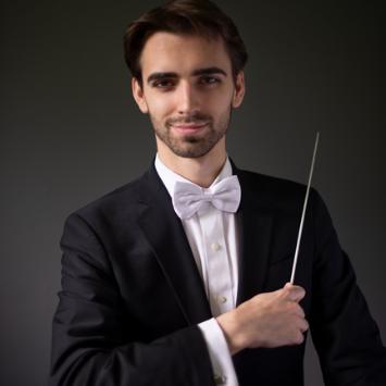 white male in tuxedo with conducting baton