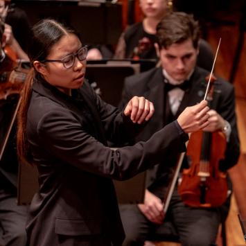 asian femal conducting an orchestra