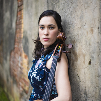 woman with brown hair in blue dress holding arm of cello