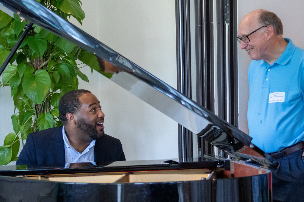 young black man playing piano and laughing with older white man in blue shirt enjoying the music