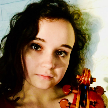 young white woman with curly long brown hair holding a cello