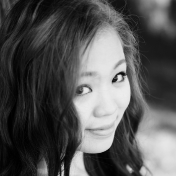 young asian female smiling at camera long wavy hair black and white photo