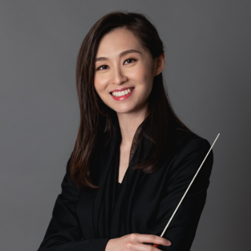 Young aisian femal in black jacket holding a conductor baton