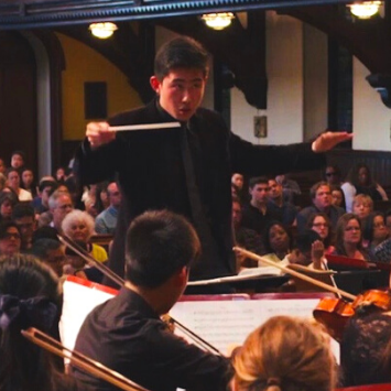 young Asian ma in black suit conducting in a church