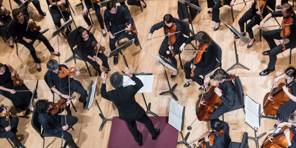 overhead photo conductor and young orchestra musicians