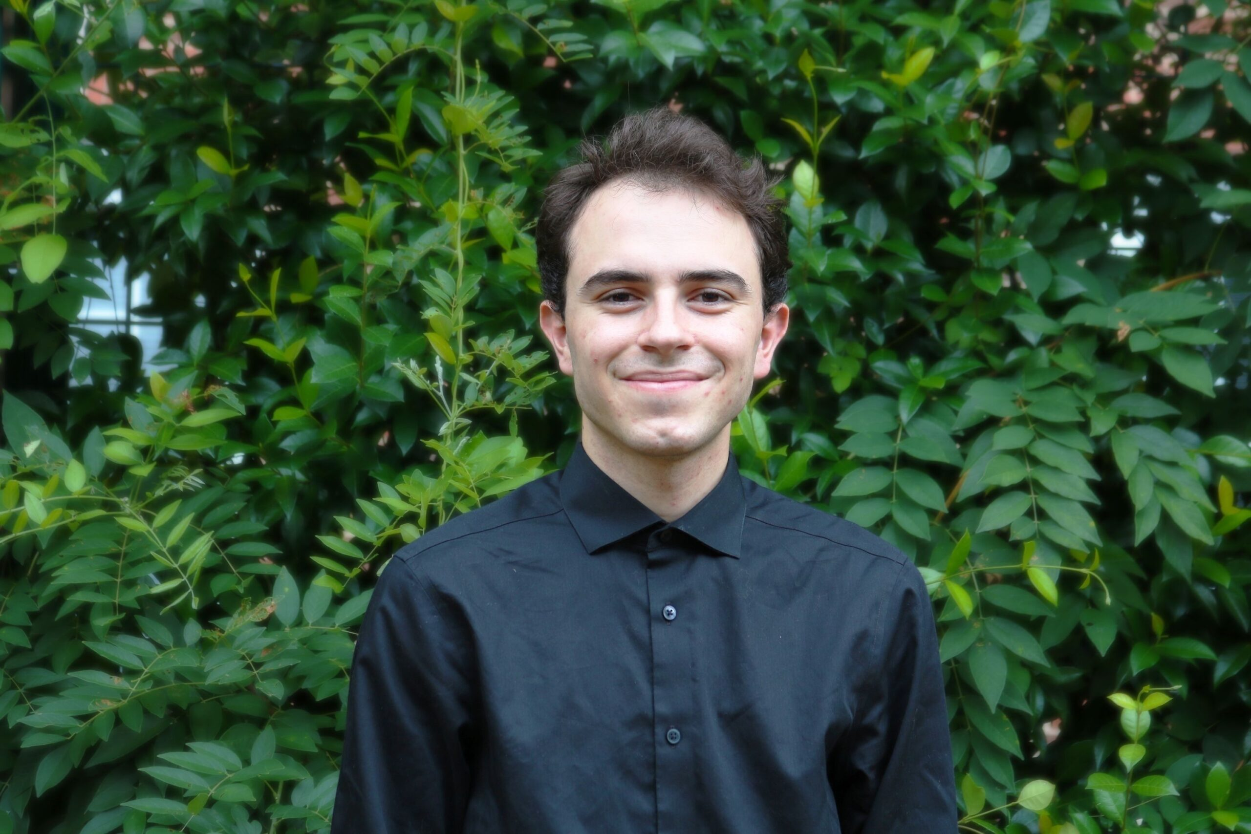 young white male in black dress shirt smiling in front of greenery wall