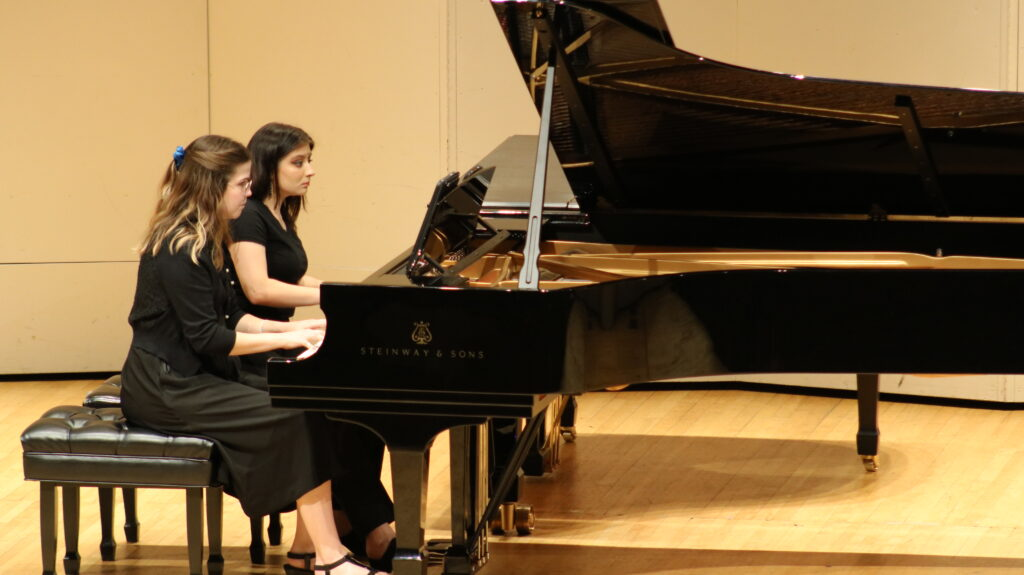 two young female pianists playing one piano