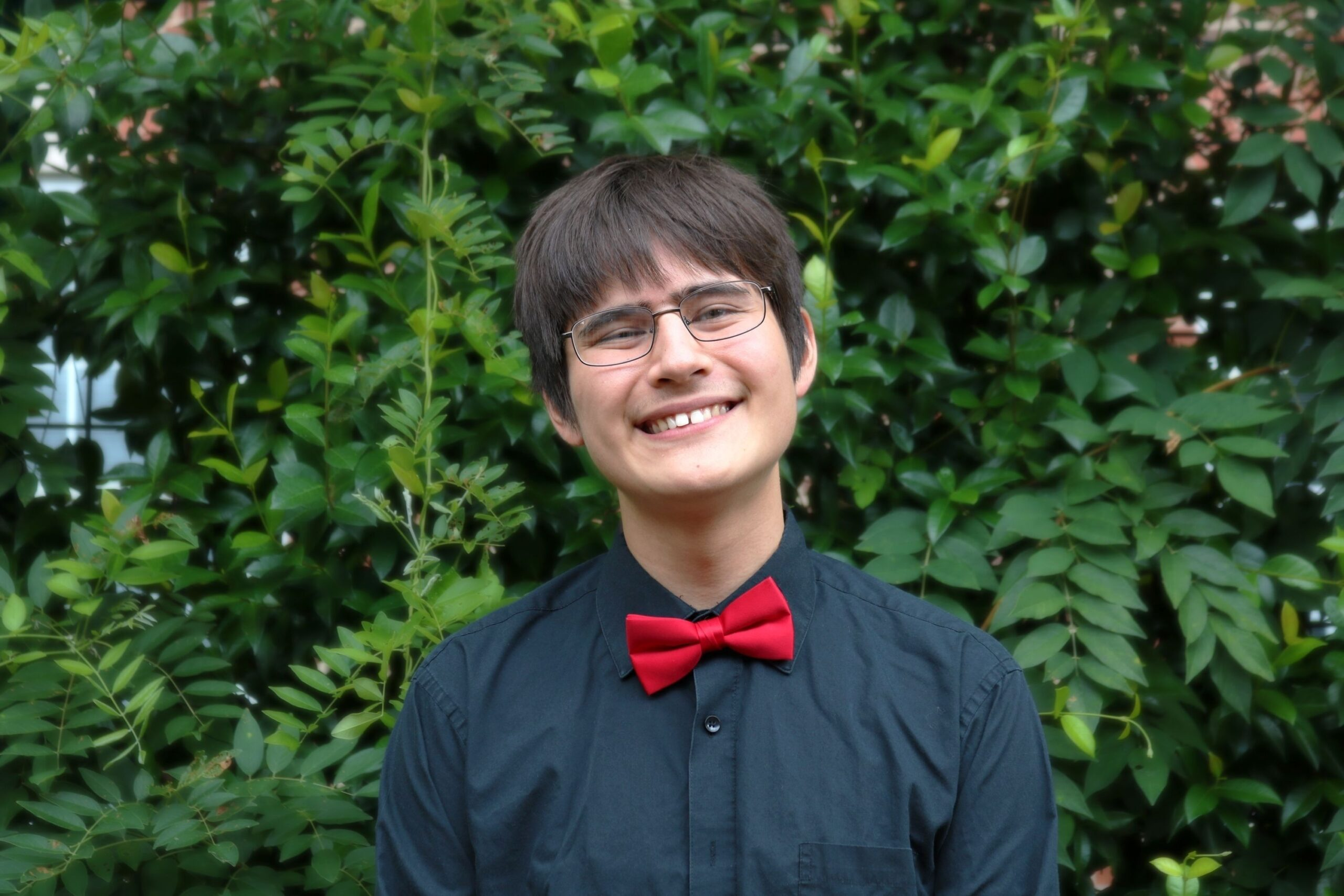 Young asian american mal in black dress shirt and red bowtie wearing eye glasses smiling broadly in front of greenery wall