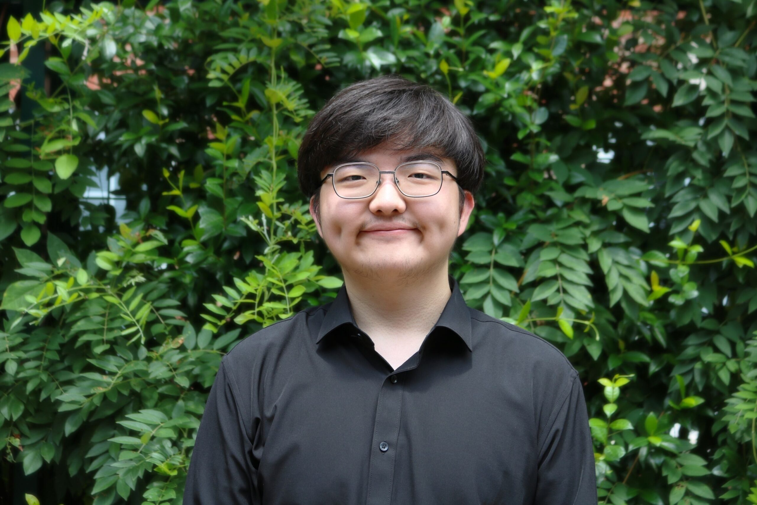 young asian man in black dress shirt with wire rim eyeglasses smiling in front of greenery wall