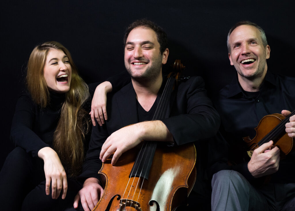 three classical musicians one female two male wearing black and laughing