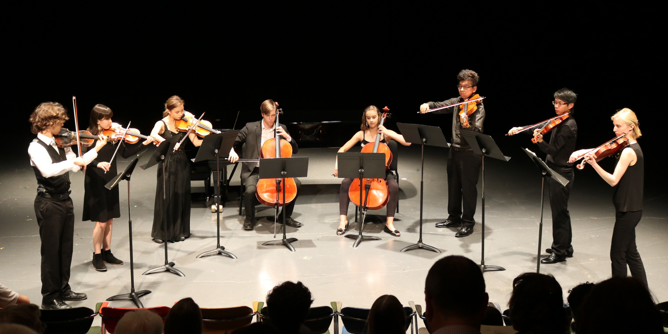 eight classical musicians standing in semi circle playing string instruments
