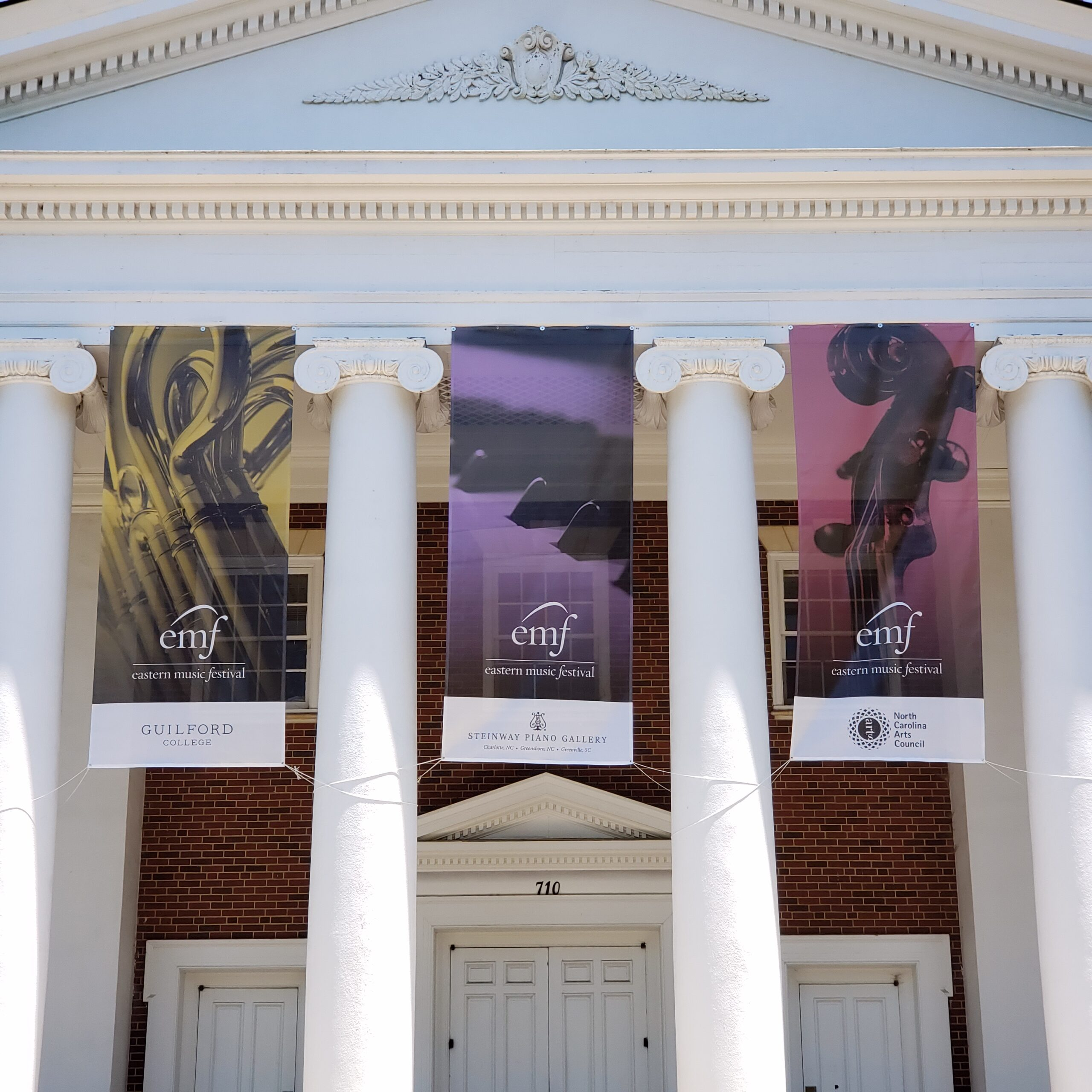 exterior doric white columns and three colorful EMF banners