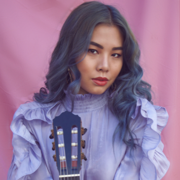 asian woman with light blue hair in lavendar blouse and pink backgrouns, holding classical guitar
