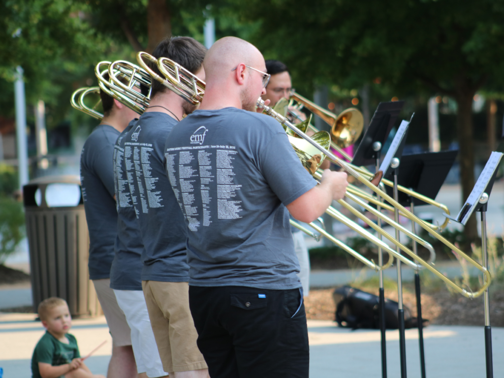 musicians in grey EFM tshirts playing trombones outside